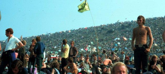 Blauer Himmel, großer Hügel, Menschen, Zelte, Festival, liegen, stehen, gelbe Fahne, weißes Hemd,